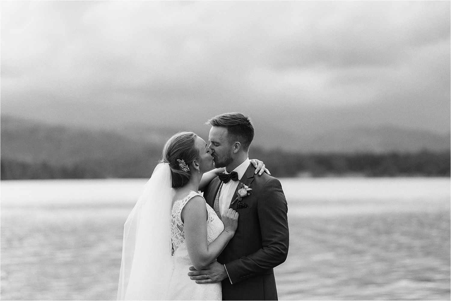 Bride and groom exchange a kiss on shores of Lake Windermere