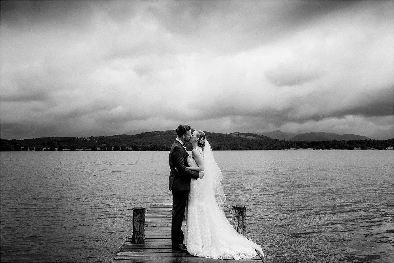 Kissing bride and groom on jetty at Low Wood Bay wedding venue, Lake Windermere