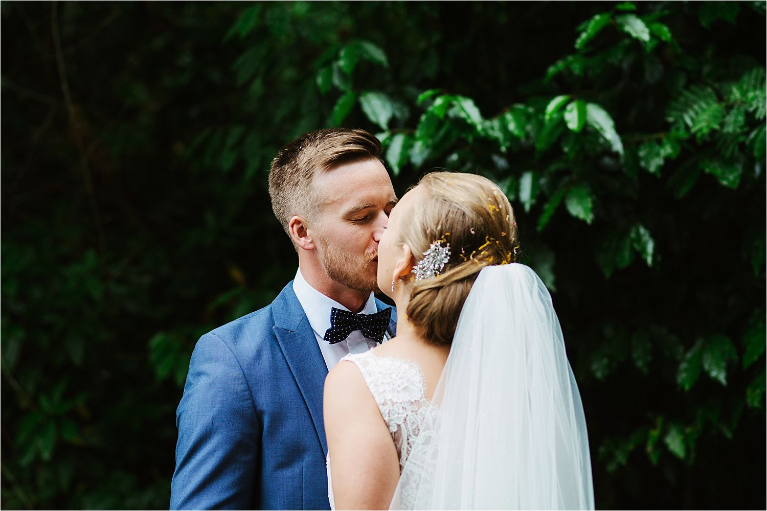 Bride and groom share a kiss in Low Wood Bay gardens