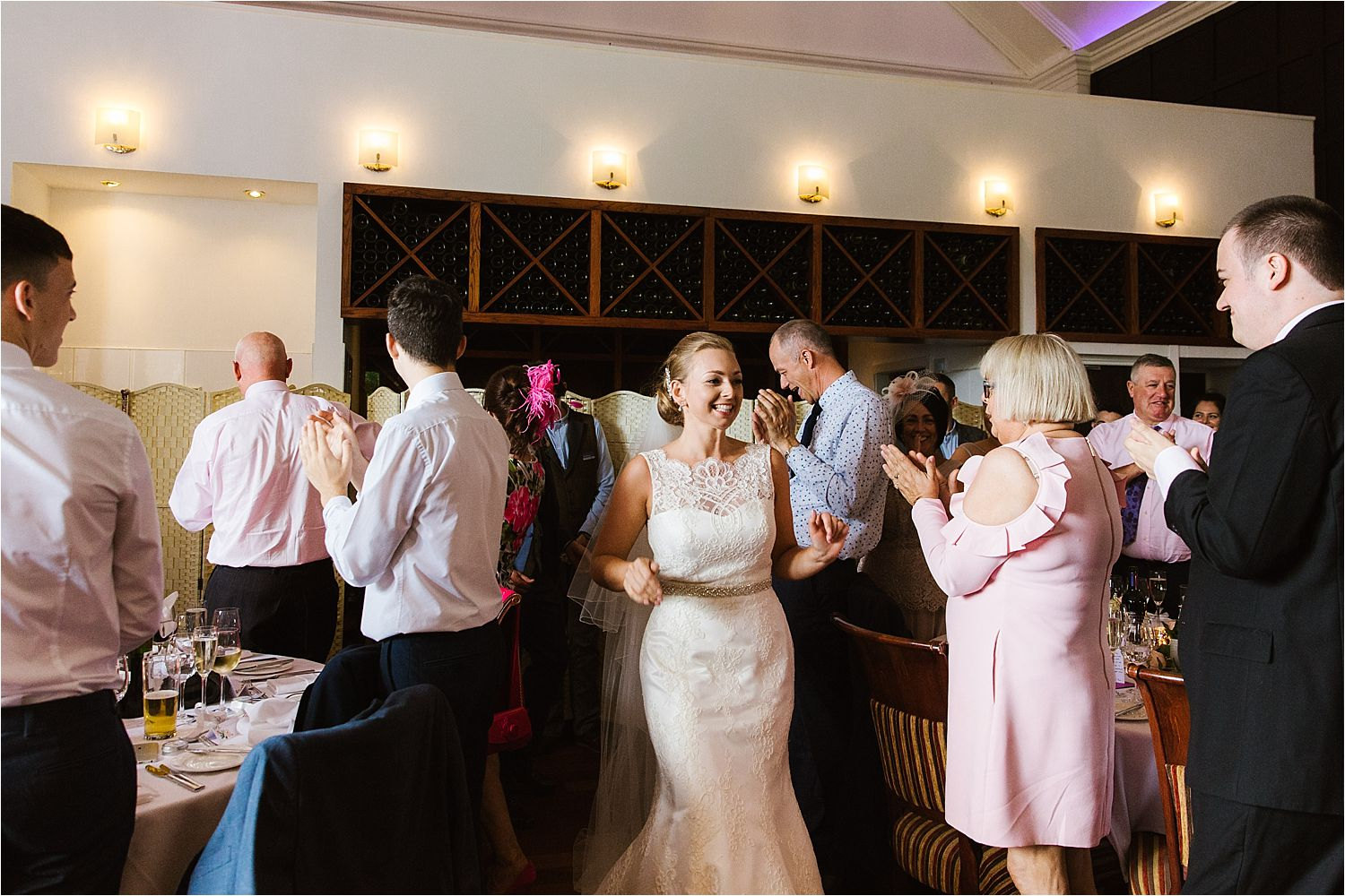 Guests welcome bride and groom into reception at Lake District wedding venue, Low Wood Bay
