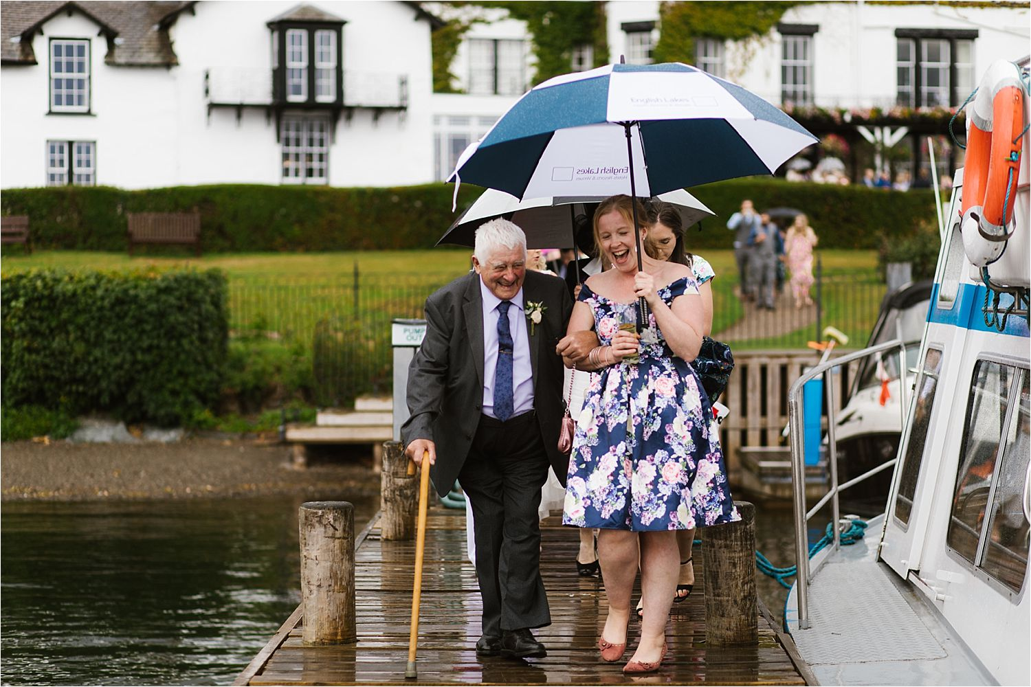 Guests with umbrellas wlaking down the jetty for a boat trip with Windermere Lake Cruises