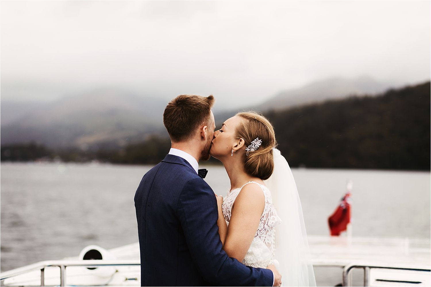 Wedding couple kissing on boat trip on Lake Windermere.