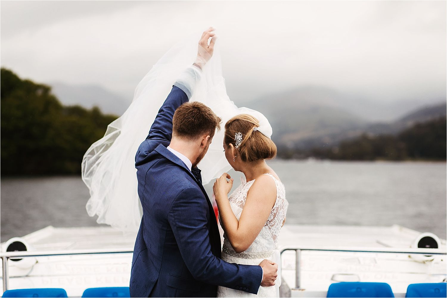 Wedding couple holding up the veil as they cruise on Lake Windermere after their Low Wood Bay wedding