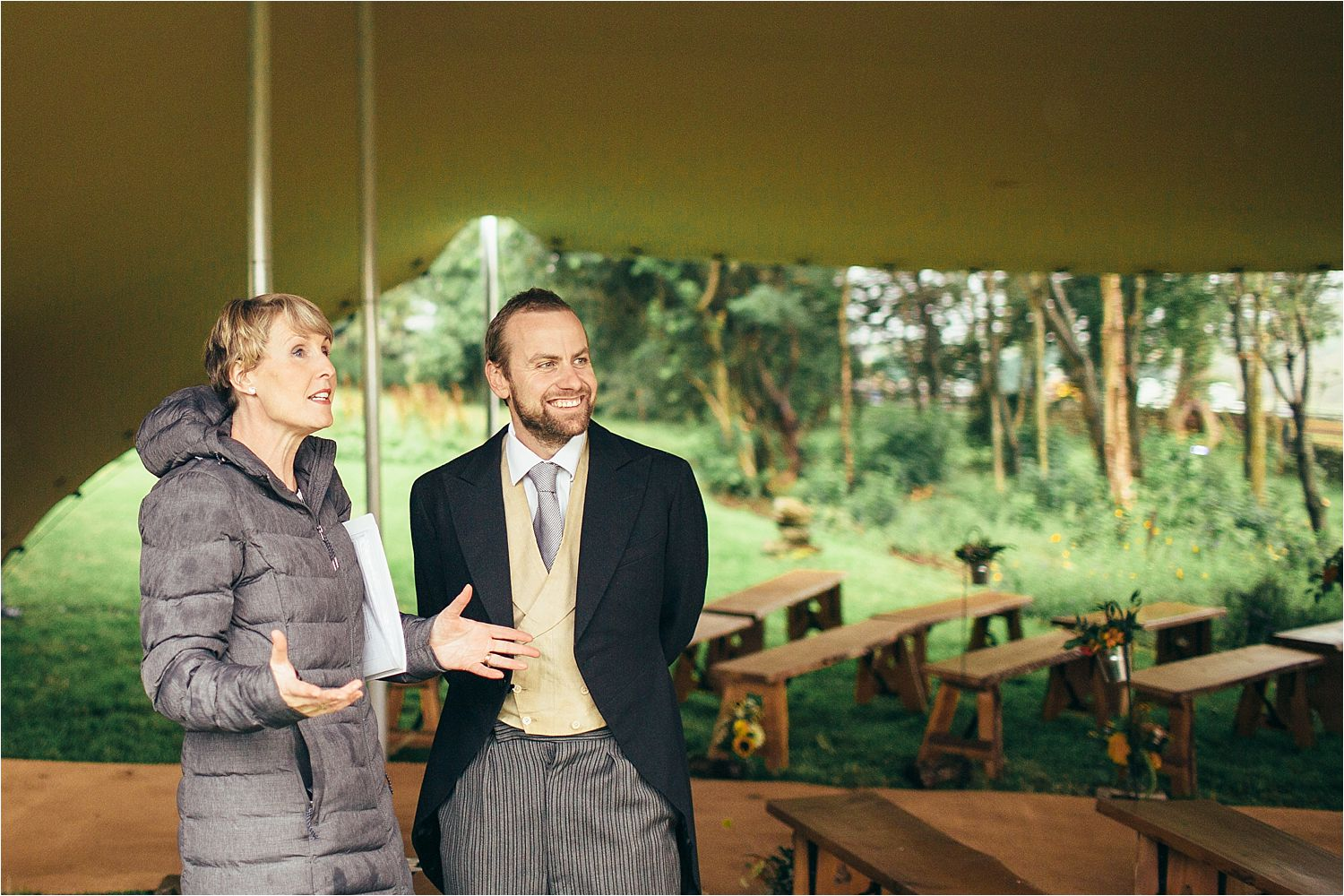 Groom and wedding coordinator discuss the weather at Manchester wedding. Wedding organised by Fabulous Together Wedding and Event Planning