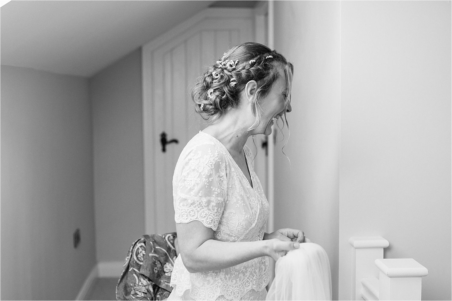 Bride laughing as she prepares her veil for fixing. Wedding dress by Elizabeth Avey Vintage Bridal Wear