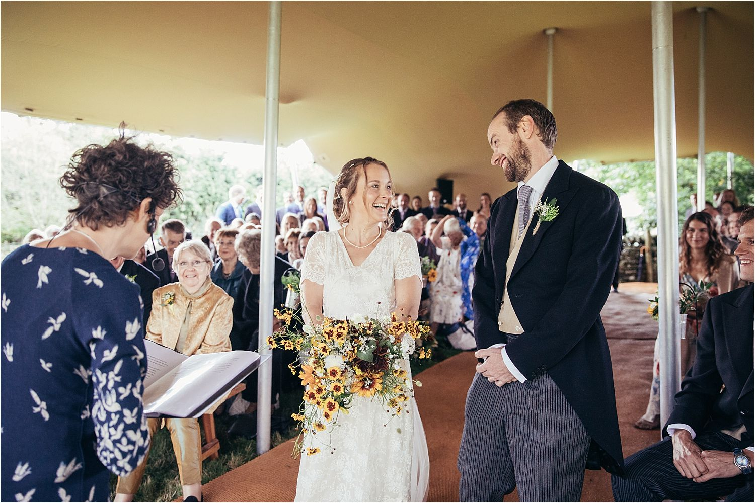 Bride and groom during ceremony in Big Chief Tipi at rural Manchester wedding