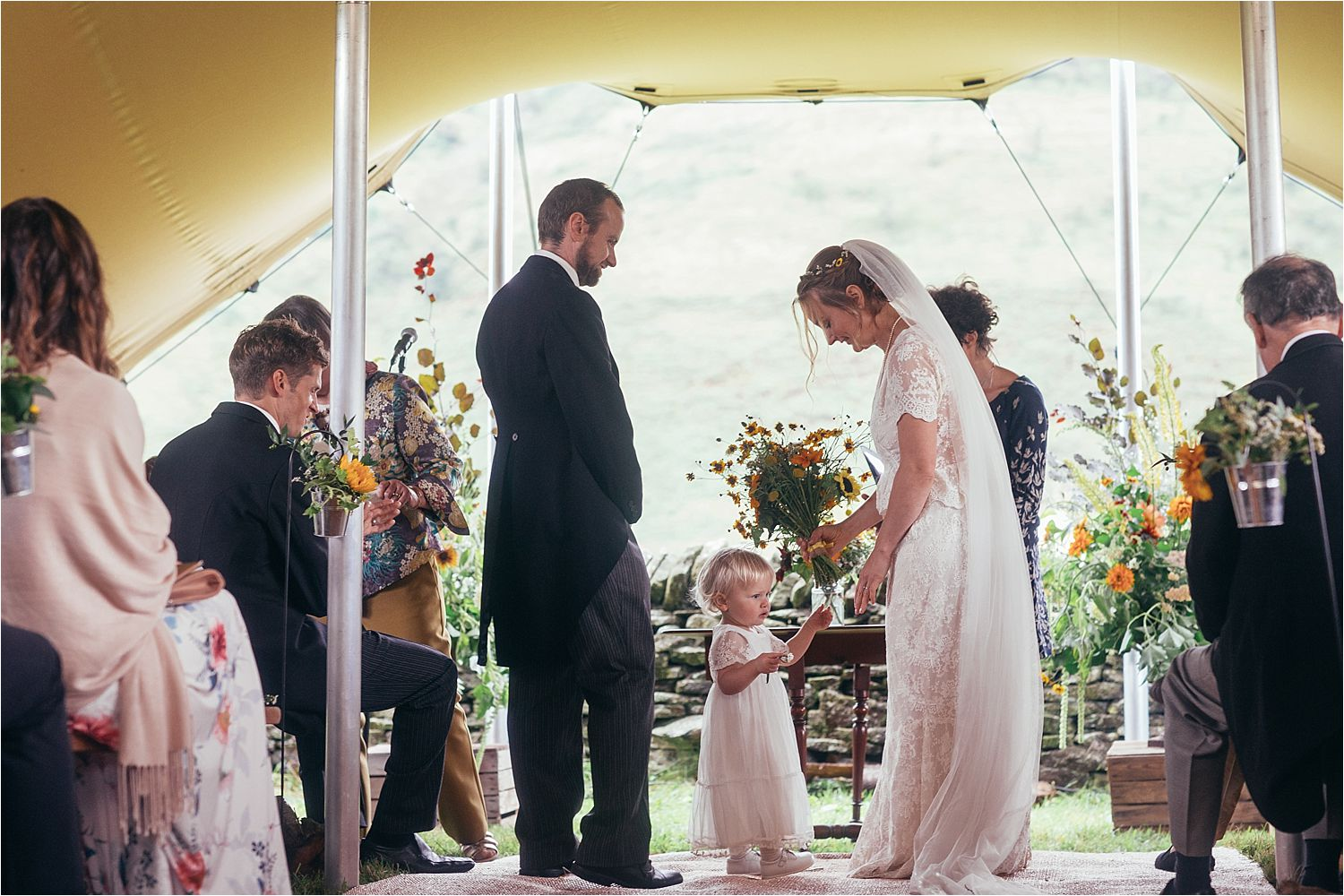 Bride, groom and flower girl at wedding ceremony in Big Chief Tipi