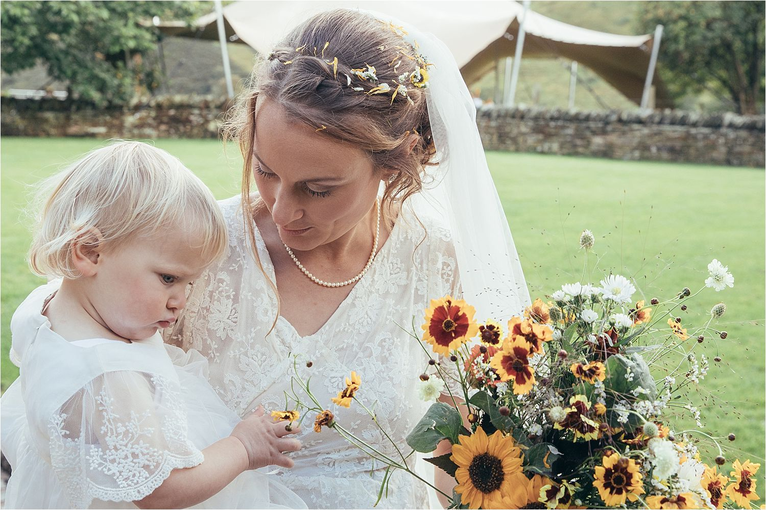 Bride and flower girl at North West tipi wedding. Flowers by Fletcher and Foley of Manchester