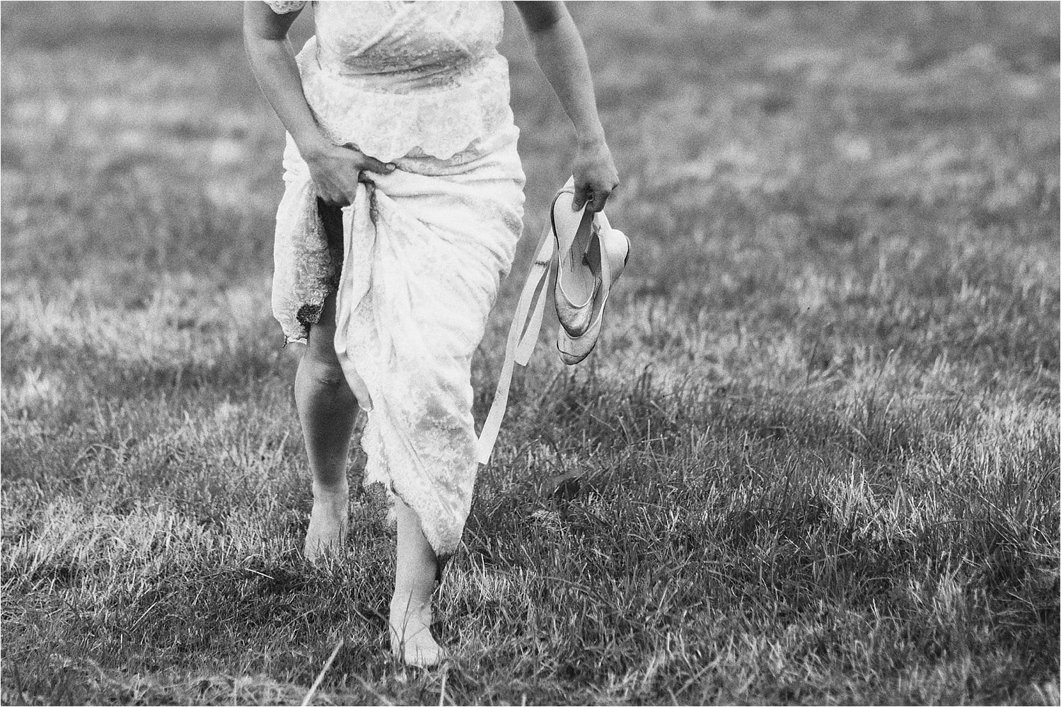 Bride crossing grass with wedding shoes in hand at rural wedding venue in Glossop