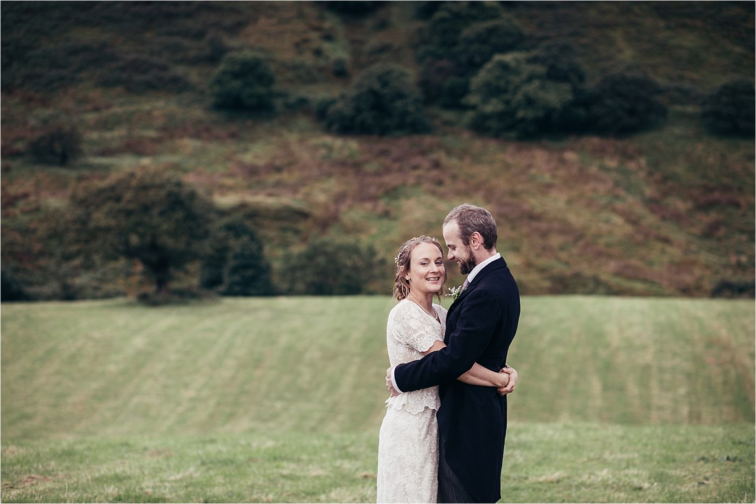 Bride and groom embrace in rural setting for Manchester wedding