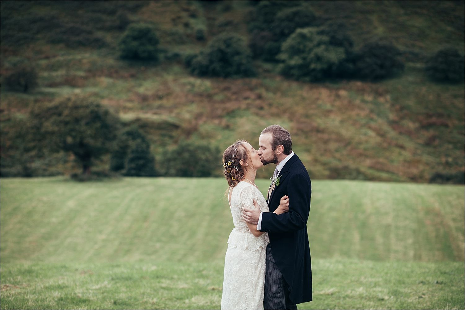 Bride and groom kissing in landscape at rural North West wedding