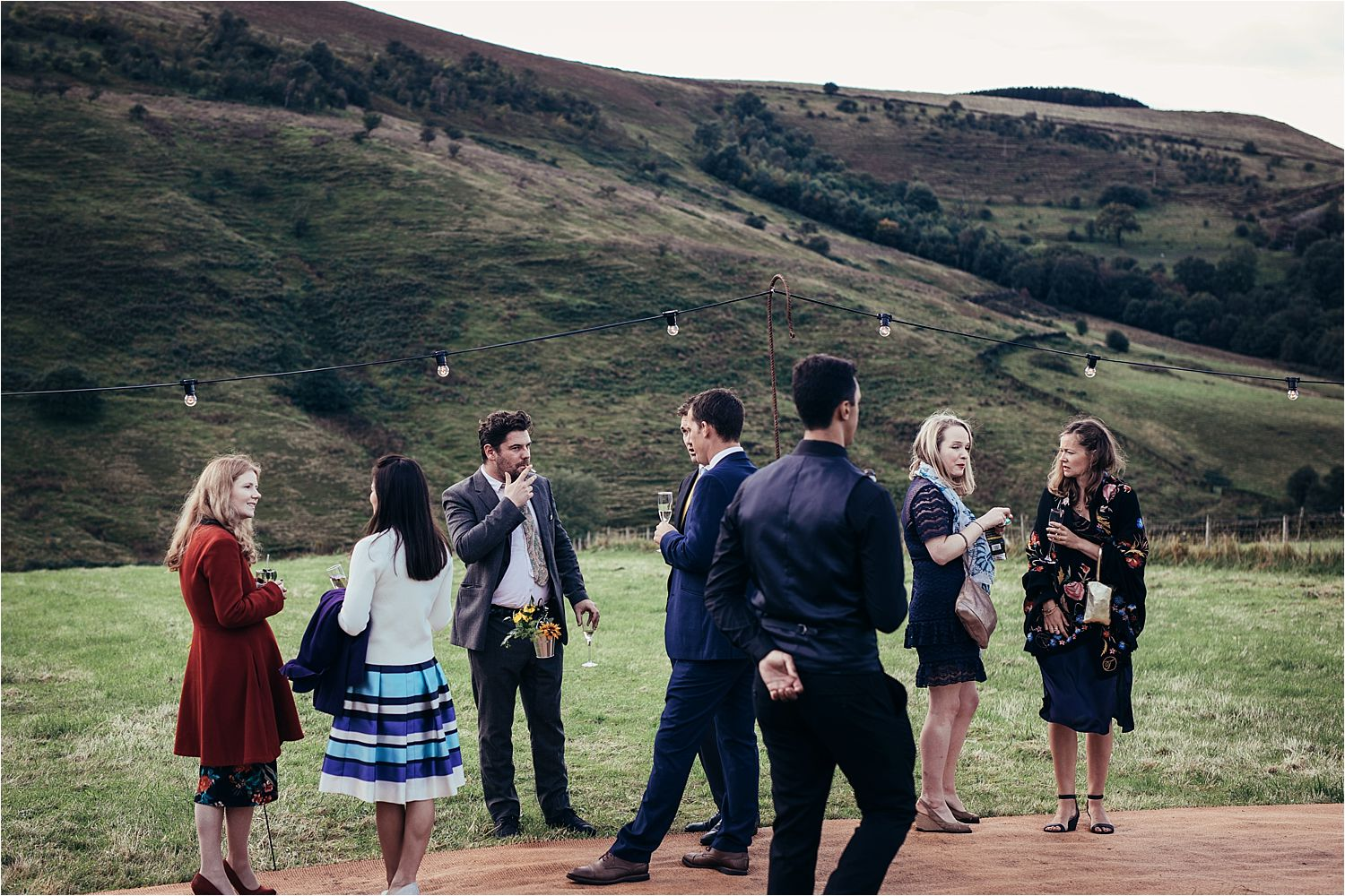 Guests mingling on the moors at rural Manchester tipi wedding