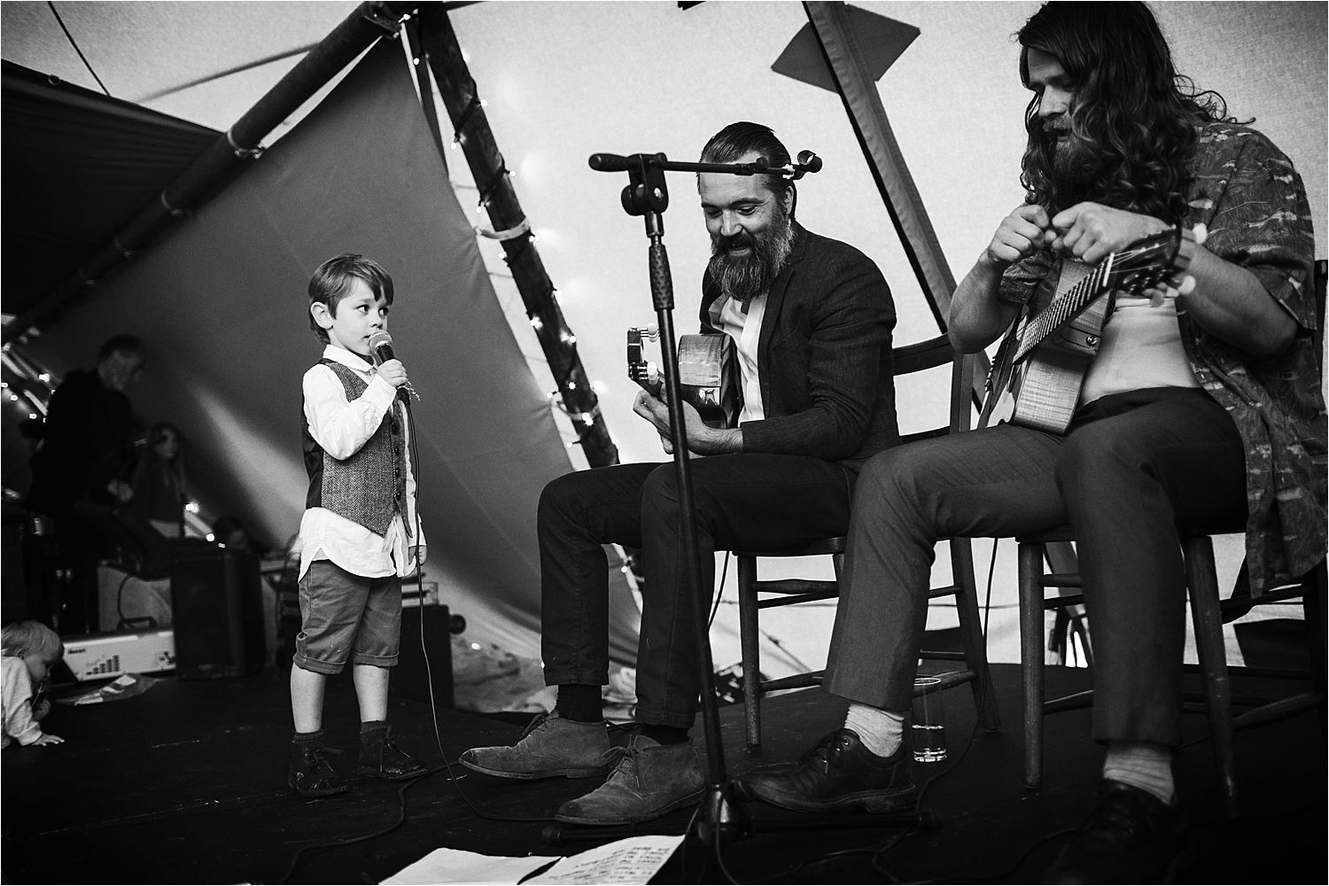 Little boy sings with band at rural Manchester tipi wedding