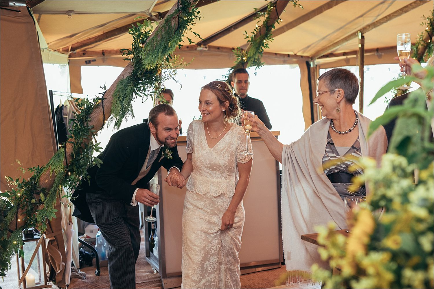 Guests raise a glass to bride and groom as they enter tipi wedding recepti. Tipis by Big Chief Tipis of Manchester