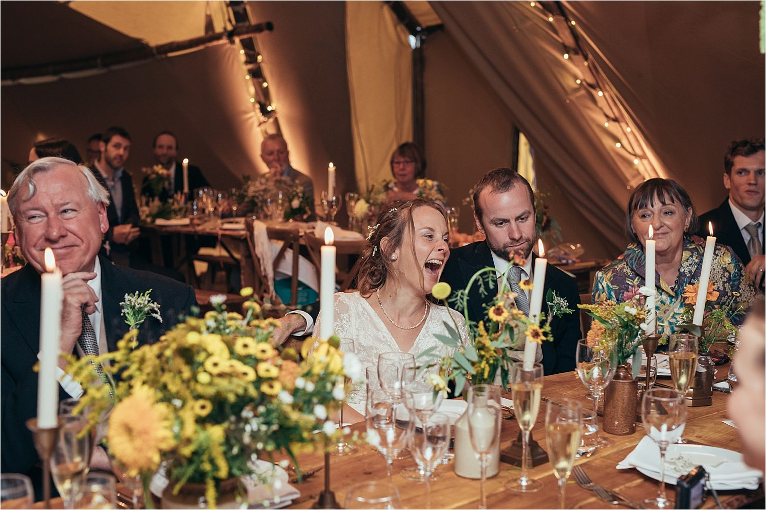 Bride's reaction to speeches at her rural Manchester tipi wedding. Flowers by Fletcher and Foley