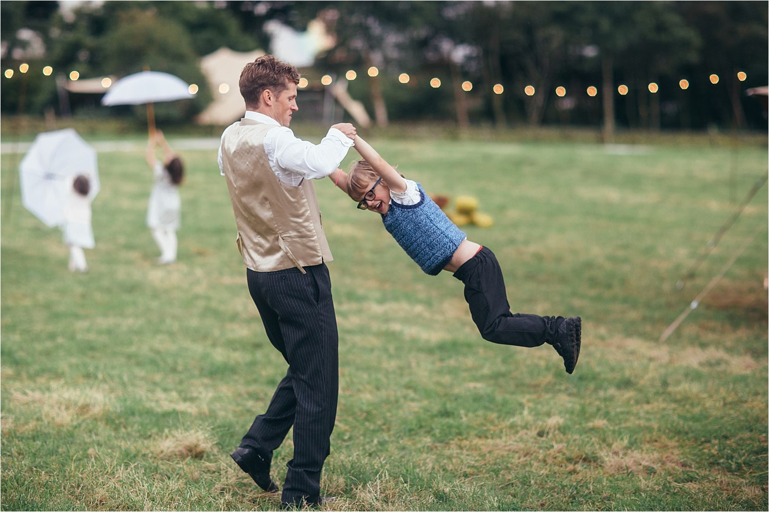 Guest swingin his son round at rural tipi wedding