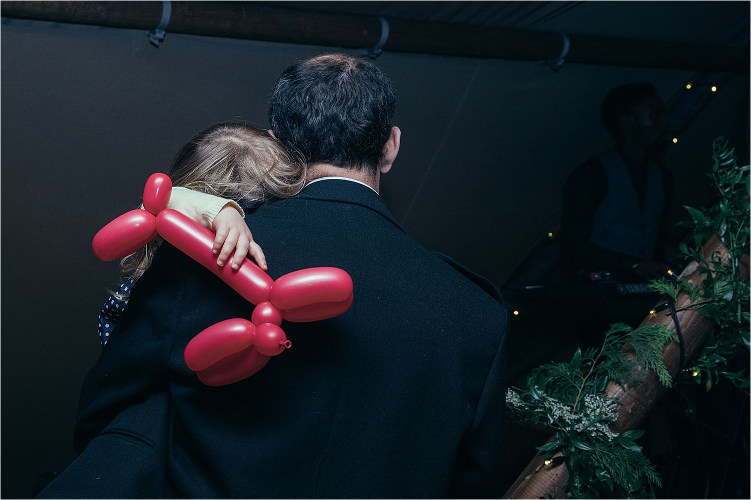 Sleeping little girl on her dad's shoulder with balloon animal at Manchester tipi wedding