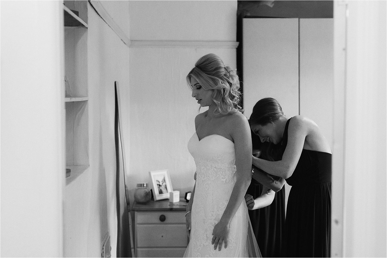 Bride is buttoned into her dress for her Cumbrian wedding