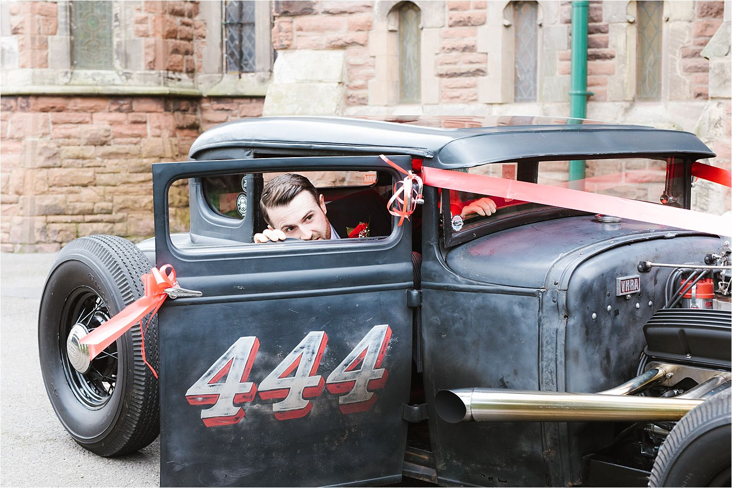 Bride groom arriving at church in vintage roadster