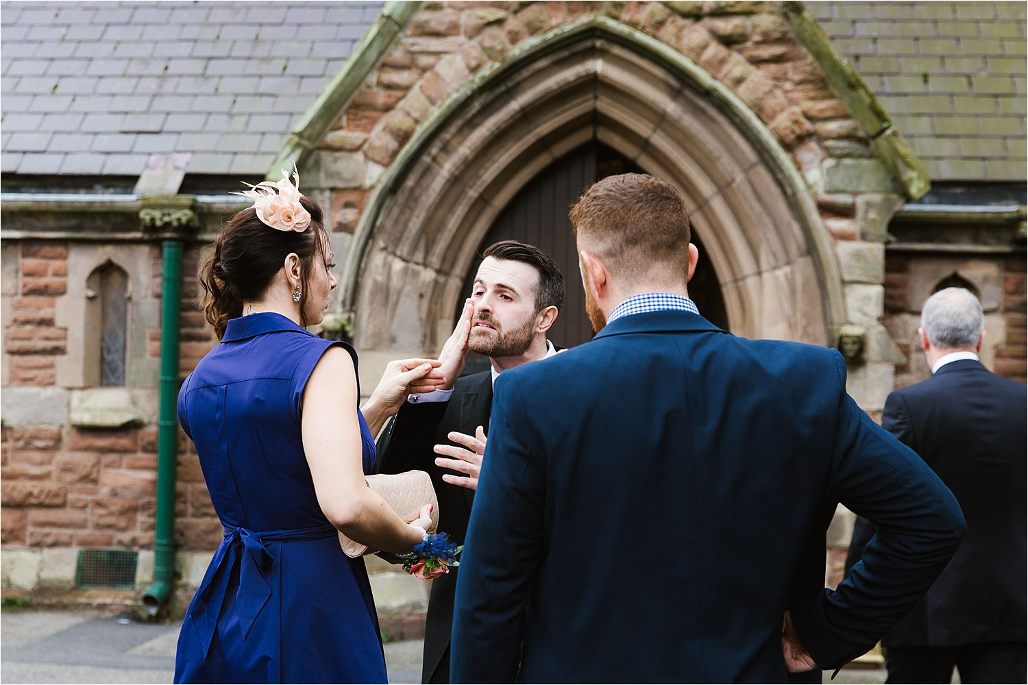 Bridegroom wiping lipstick off cheek outside church before Cumbrian wedding ceremony
