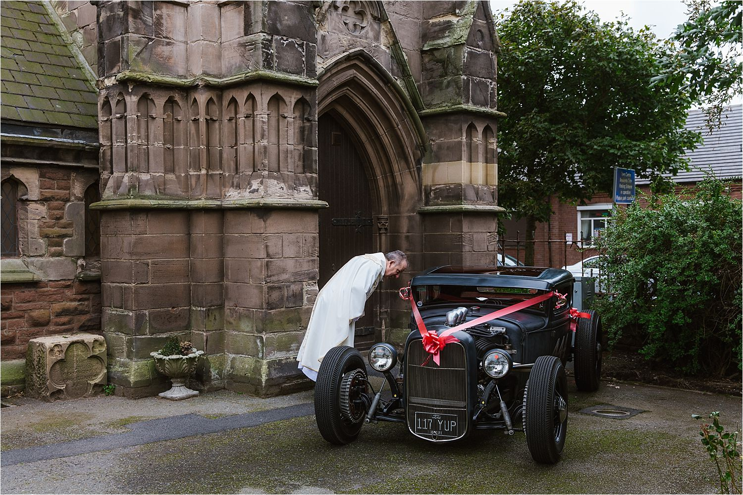 Vicar inspects the vintage roadster car outside church prior to wedding ceremony