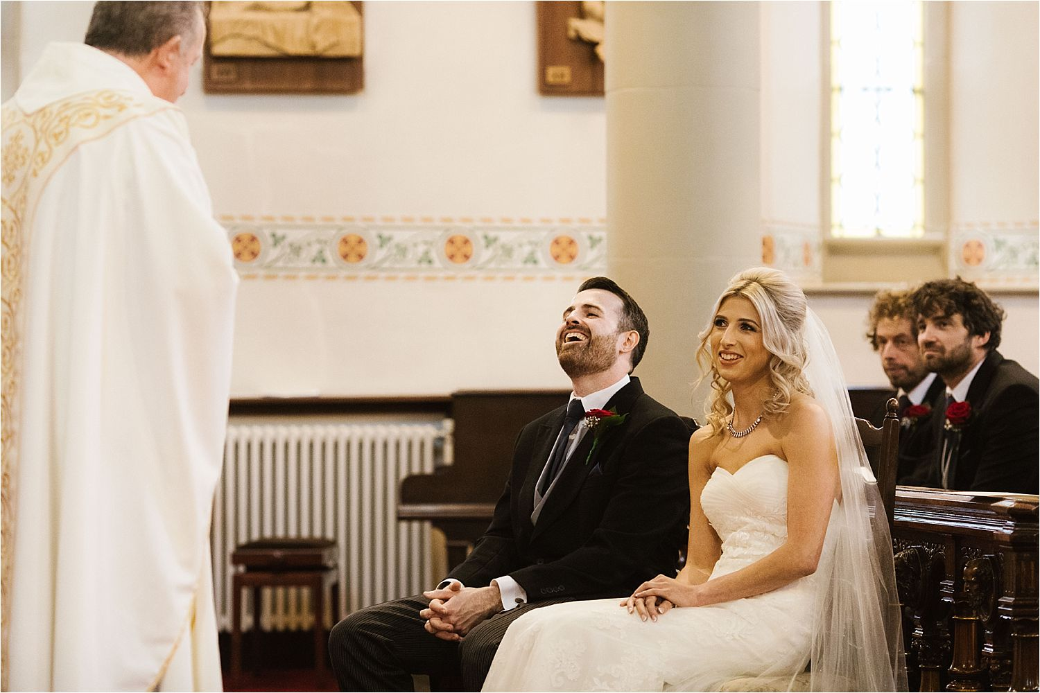 The vicar jokes with the bride and groom at their North West wedding
