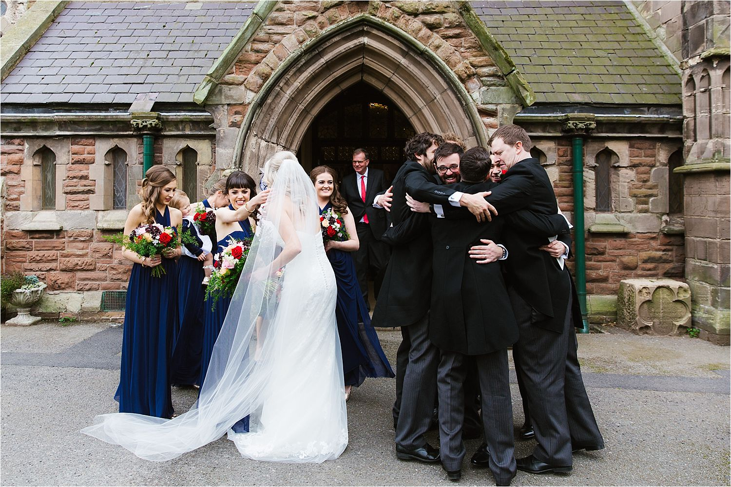 Groom in group hug with his friends outside church after his wedding