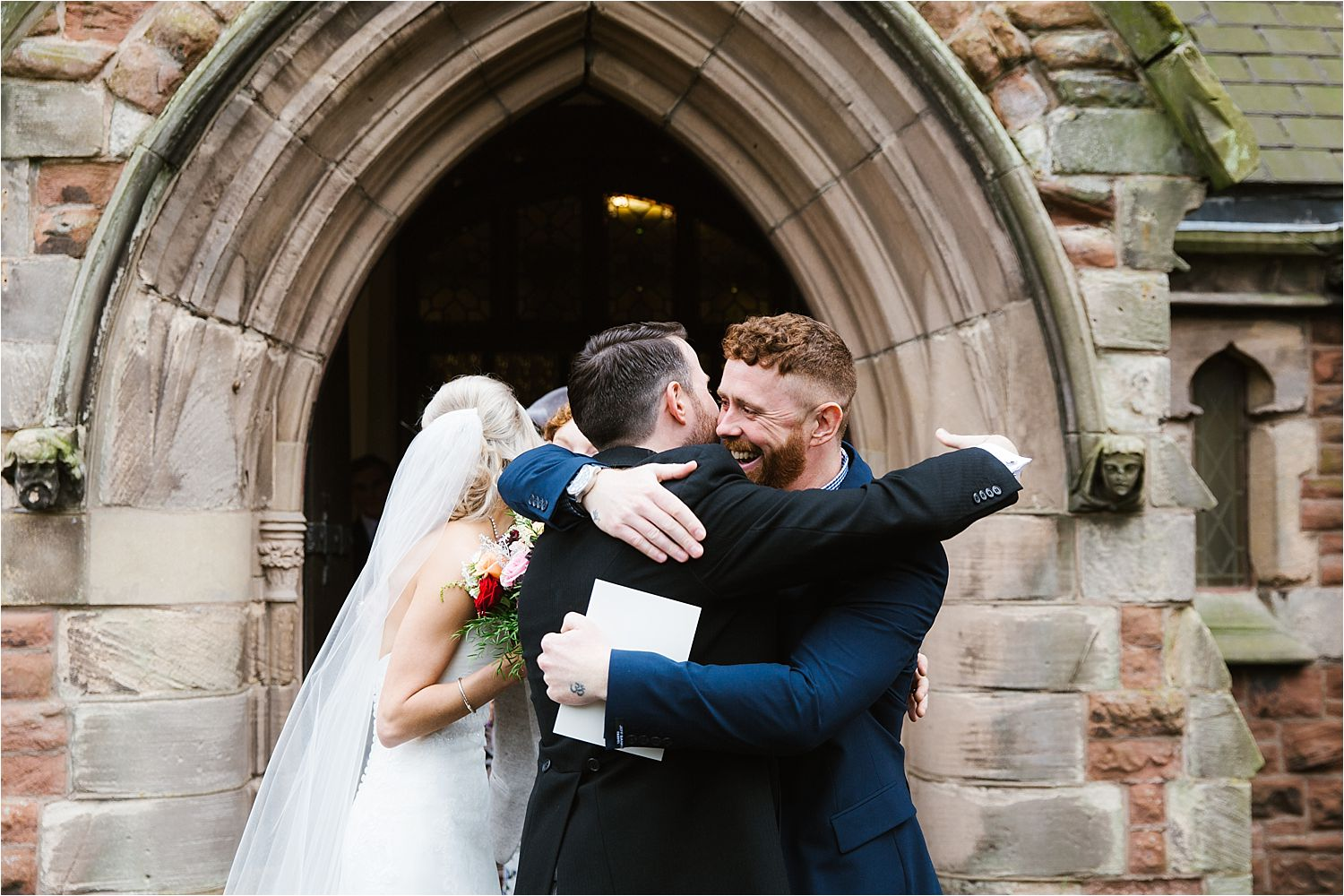 Bride and groom embrace guest outside church