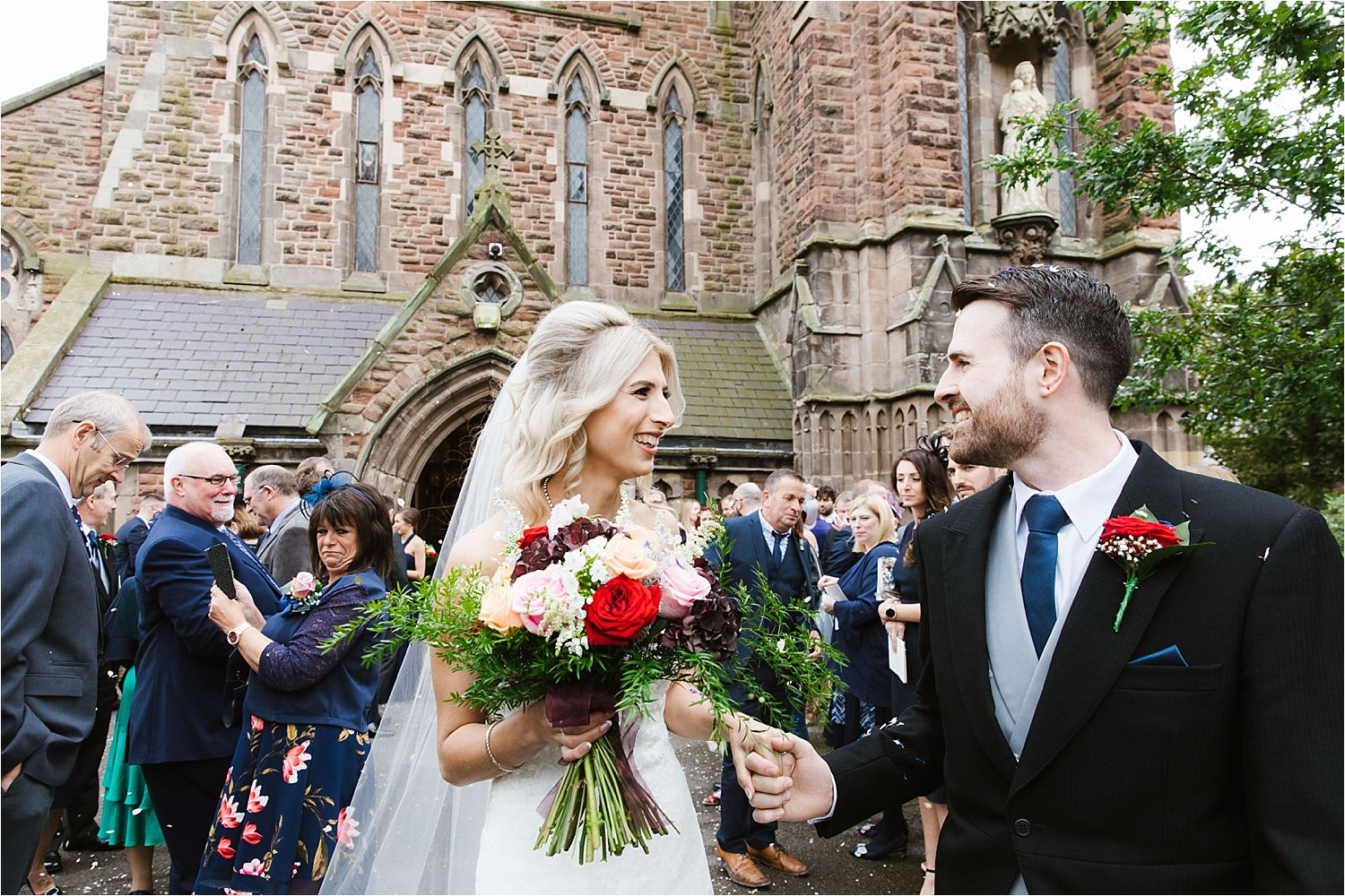 Bride and groom outside church. Bridal bouquet by Deborah's Florist Barrow