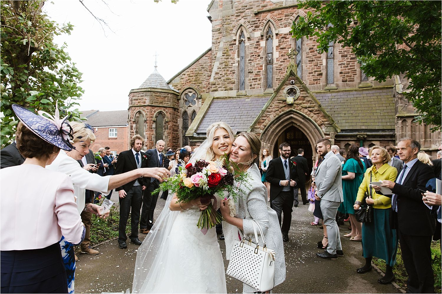 Bride greets friend outside church. Bridal bouquet by Deborah's Florist, Barrow