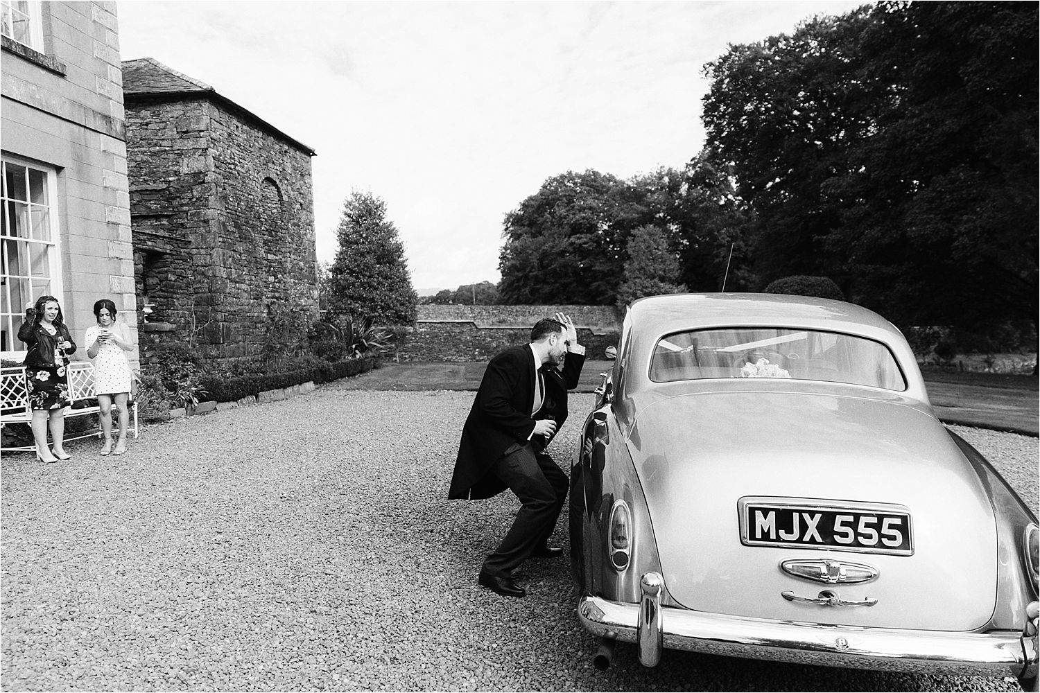 Bridegroom straightens his hair in the window of the classic wedding car at Belmount Hall