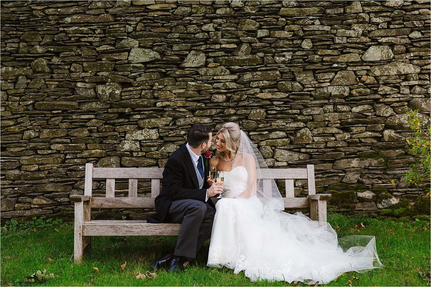 A quiet moment on a bench together to enjoy a glass of champagne before the reception starts at Lake District wedding venue, Belmount Hall