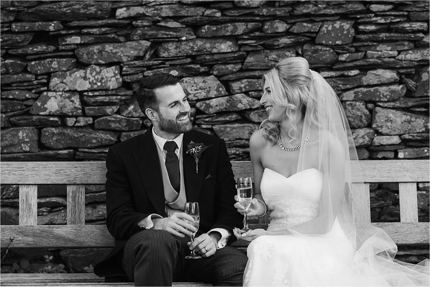 Bride and groom share a quiet moment and a glass of fizz after their Cumbrian wedding