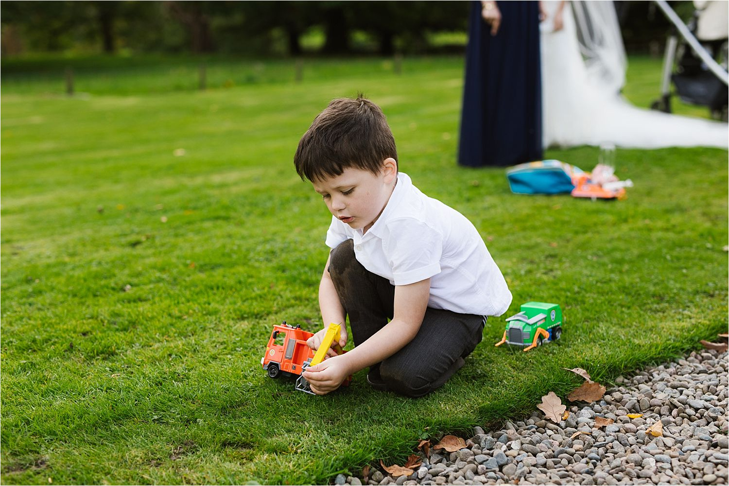 Little boy playing with tractor on the grass at Belmount Hall wedding