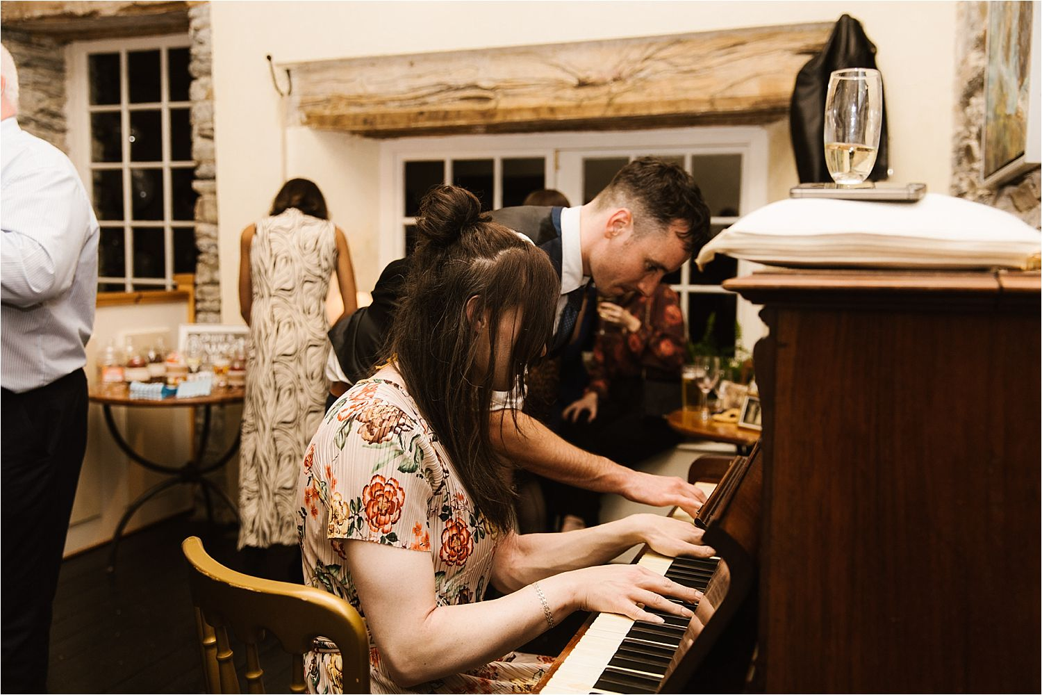 Guests playing the piano at Lake District wedding