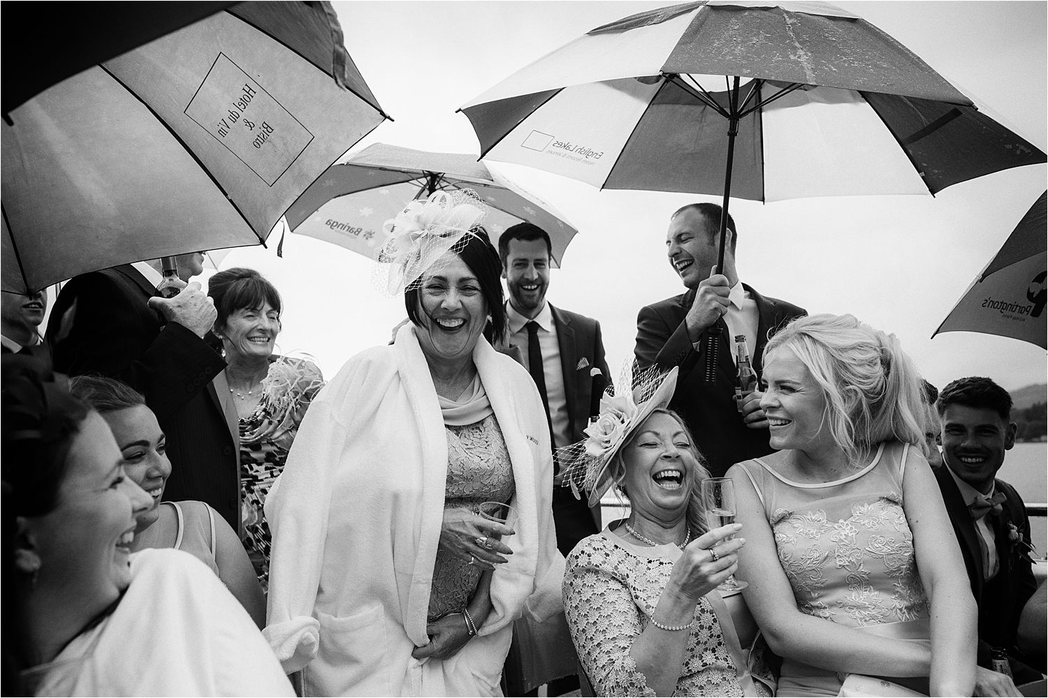 Laughing guest ignoring the rain and enjoying a cruise across Lake Windermere from Low Wood Bay wedding