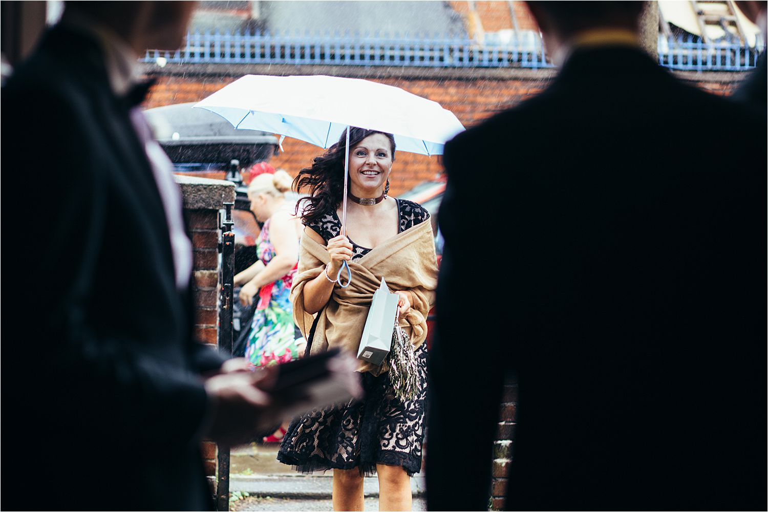 wedding guest with umbrella arrives for rainy north west wedding