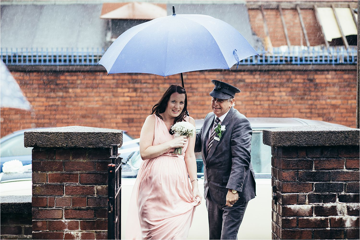 Chauffeur with umbrella shields bridesmaid from heavy rain as she arrives at church