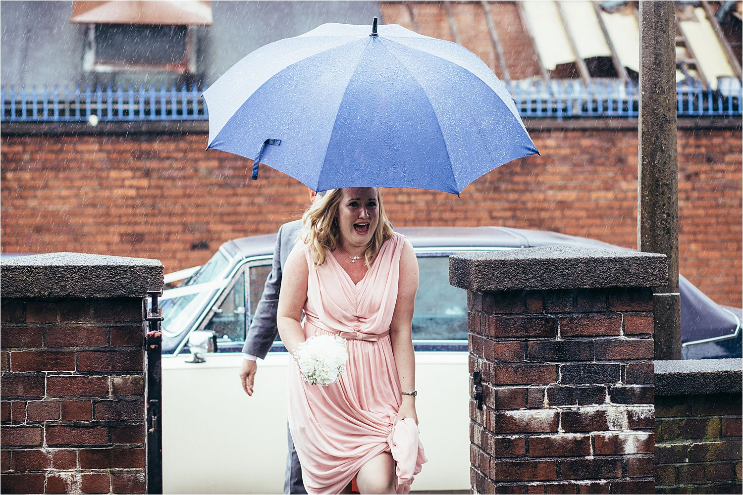 Bridesmaid arrives at church in heavy rain for North west wedding