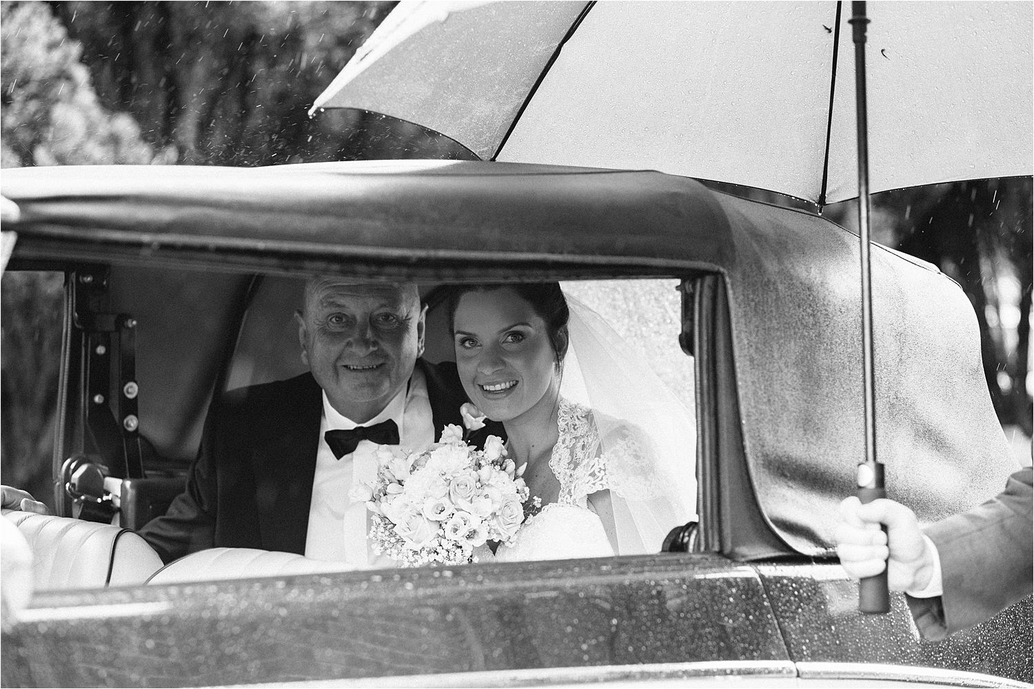 Bride and her father arrive in vintage car for wet Lake District wedding
