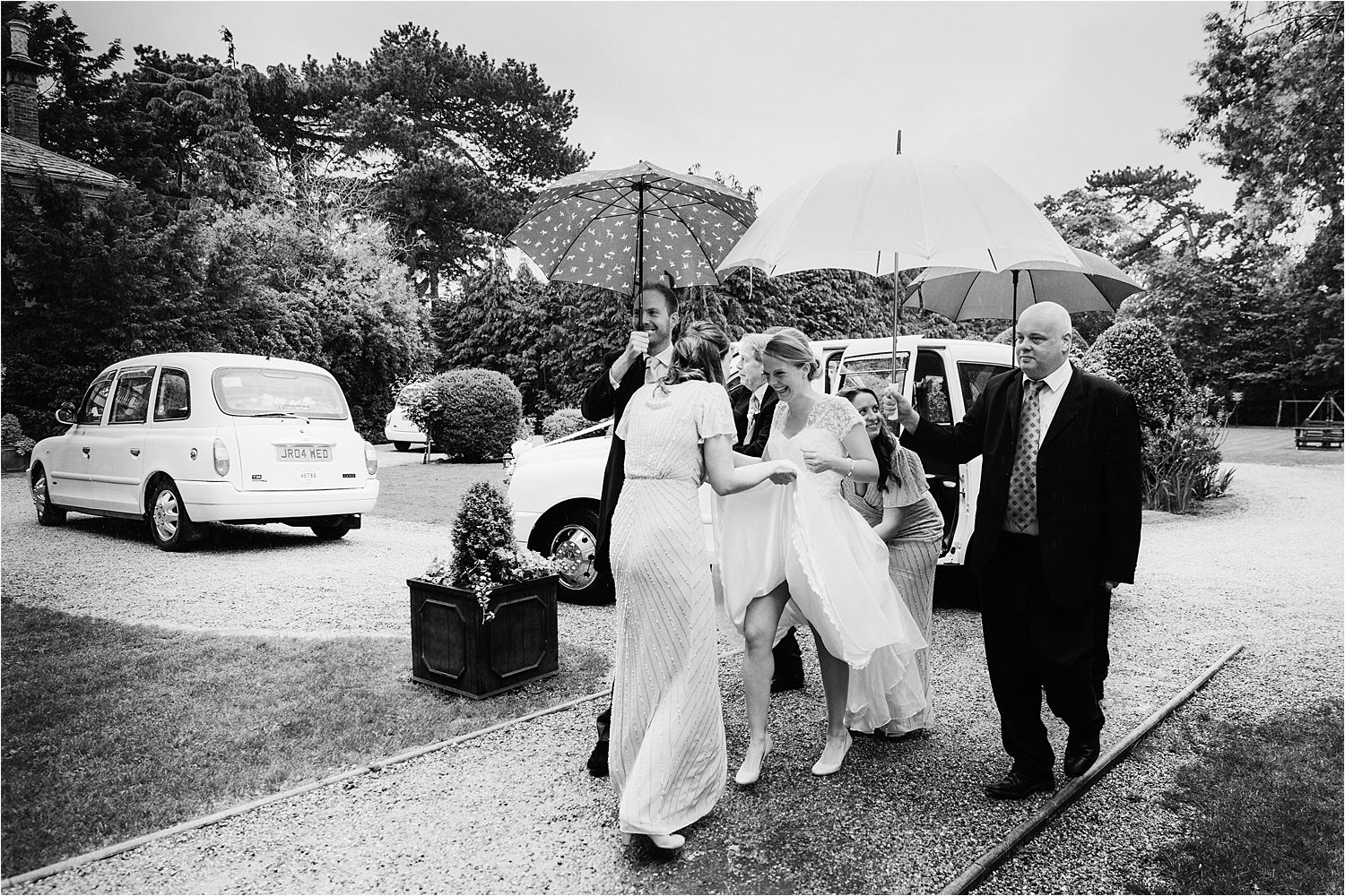 Bridesmaids holding up bride's dress as she walks to ceremony on rainy wedding day.